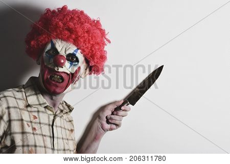 a scary evil clown wearing a dirty and ragged plaid shirt with a big knife in his hand against an off-white background with a blank space on the right