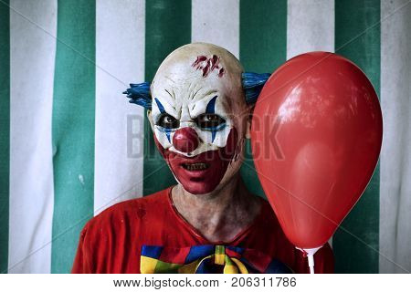 closeup of a scary evil clown wearing a dirty costume and holding a red balloon, with the circus tent in the background