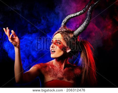 Mad satan woman on black magic ritual of in hell. Witch reincarnation mythical creature on Sabbath. Devil on Halloween. Astral beings are among us. Make-up for night club. Visions of drug addict.