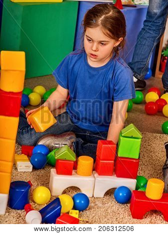 Children building blocks in kindergarten. Group kids playing toy on floor. Top view of interior preschool. Kid is keen on playing dice. Logical constructor.