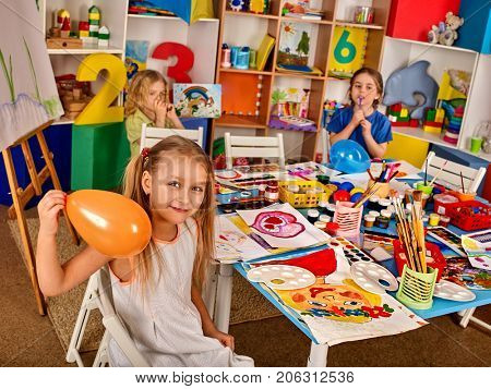 Break school in painting class. Small student paint on easel in art school class. Physical education of little girl playing with balloon. Children indulge.