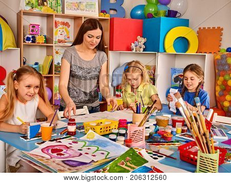 Kids playroom organization of children painting and drawing in kid's club. Craft lesson in primary school. Kindergarten teacher and students work together. Preparing for a children's art exhibition.