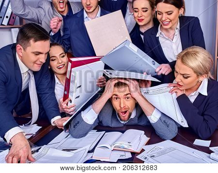Business people office. Team people are unhappy with their leader. Intern man manager littered with work and does not cope with his duties. Businessman in stress. New employee on first working day