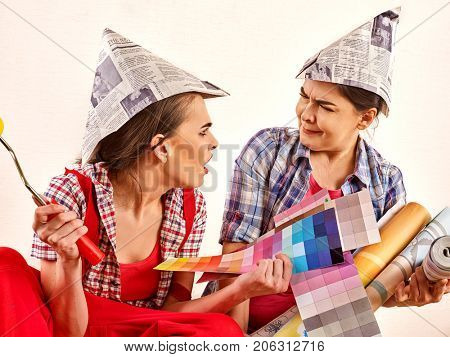 Repair home women holding color guide for wallpaper. Elderly mother and young daughter renovation apartment on isolated. Together have fun. Quarrels in family due to repairs.