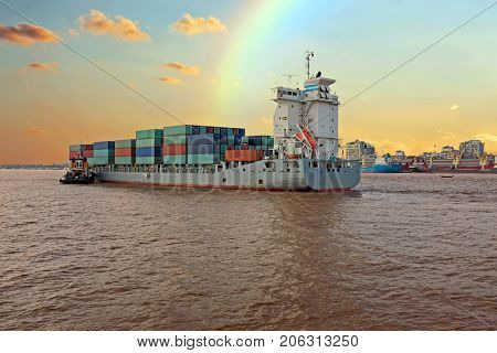Containership on the Yangon river near Yangon in Myanmar at sunset