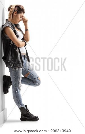 Full length profile shot of a depressed punk girl leaning against a wall isolated on white background