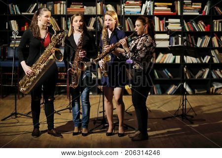 Four young pretty women with wind instruments perform in room with books