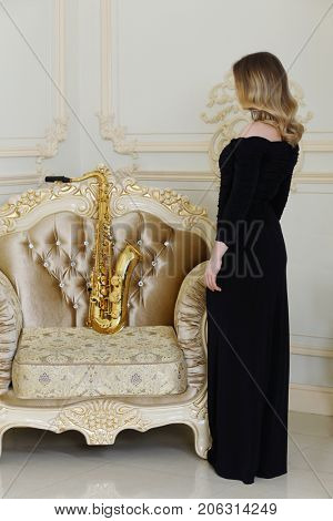 Woman in black stands near armchair with big sax sits in baroque studio, back view