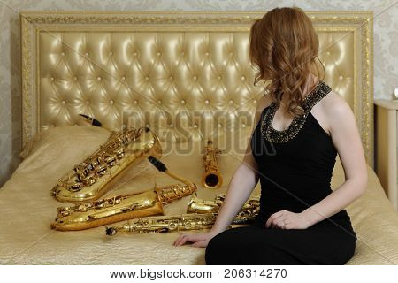 Woman in black dress sits with sax on bed with wind instruments in studio