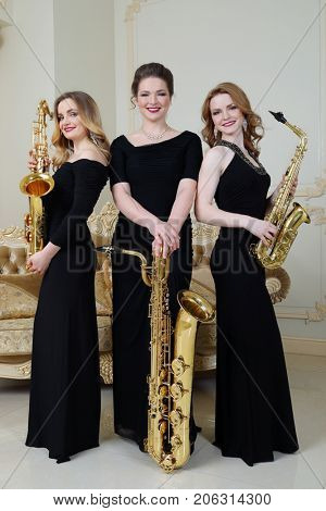 Three women in black dresses stands with saxophones in studio with couch