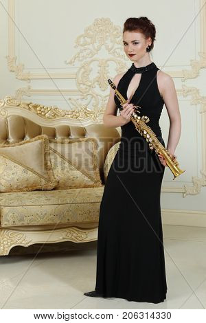 Pretty woman in black dress stands with sax in baroque studio with sofa
