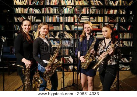 Four young pretty women pose with wind instruments in room with bookshelves