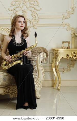 Pretty woman with sax sits on armchair in baroque studio with molding on walls