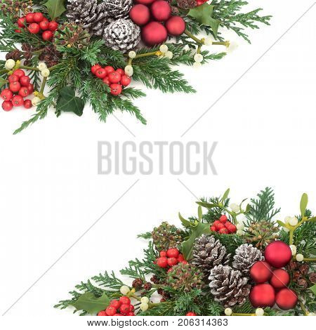 Christmas background border with red bauble decorations, holly, ivy, mistletoe, cedar and juniper leaf sprigs and pine cones over white.