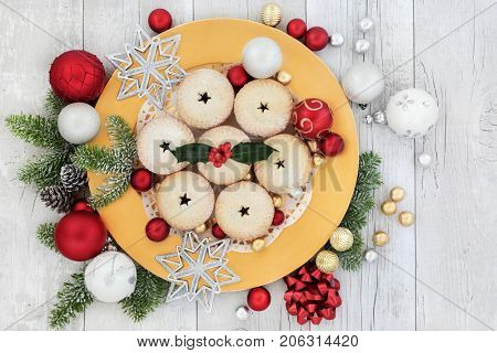Christmas mince pies on a gold plate with holly, fir, red and white bauble decorations with foil wrapped chocolates on rustic wood background.