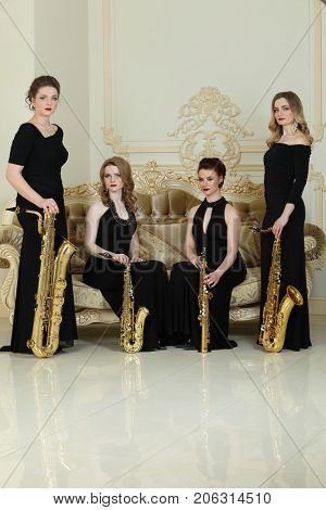 Four women in black dresses pose with saxophones near couch in studio
