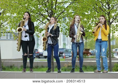 Four young pretty women in jeans play saxophone outdoor at spring day
