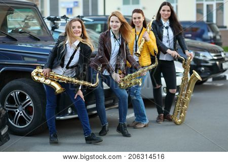 Four women poses with wind instruments outdoor near cars, focus on left woman