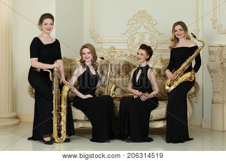 Four women in long dresses smiles with saxophones near couch in studio