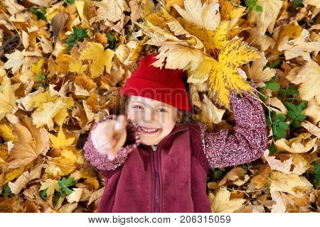 girl lie on back in autumn forest on yellow leaves background