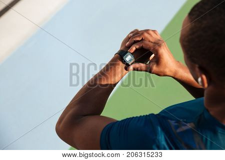 Top view close up of a fit african sportsman looking at his wrist watch while standing on a track field outdoors