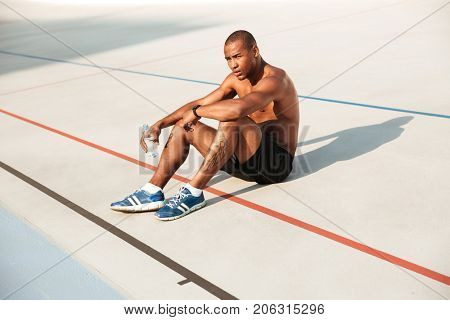 Half naked young african sportsman resting while sitting on a ground at the track field with water bottle