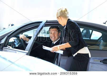 successful business man sitting behind the wheel of a new car