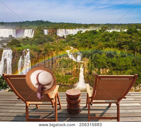 Two comfortable wooden chaise lounges face waterfalls. On one hangs an elegant straw female hat Concept of active and eco-tourism. Incredible exotic waterfalls of Iguazu in South America
