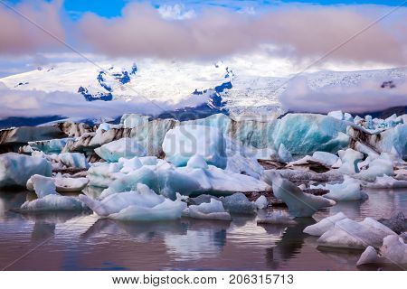 Icebergs and ice floes are reflected in the smooth water surface. Drift ice Ice Lagoon - Jokulsarlon, Iceland. The concept of extreme northern tourism