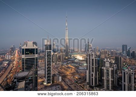 DUBAI, UAE - JAN 9, 2017: Evening Millenium Tower and Burj Khalifa, Executive Towers at night, Burj Khalifa - skyscraper in height of 828 meters in Dubai, tallest structure in world