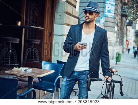 Young man on street. Trendy young man walking on street with bicycle using smartphone