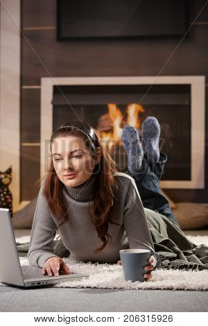 Woman Portrait. Young woman lying on floor in front of fireplace, using laptop computer, holding tea cup.
