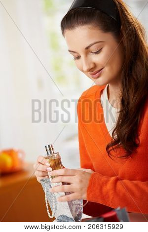 Young woman sitting at table opening gift, looking down, smiling.