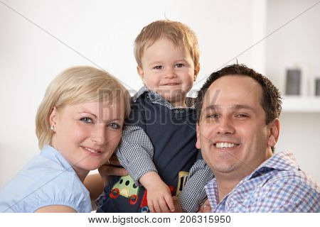 Family Portrait. Happy family of two parents and one child looking at camera, smiling.