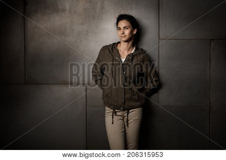 Woman Portrait. Adult woman leaning against dark wall looking at camera, smiling.