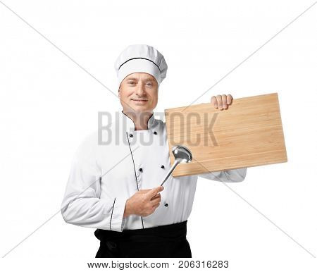 Male chef in uniform holding soup ladle and wooden board on white background