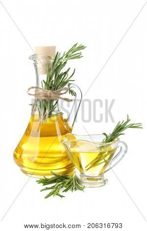 Jug and gravy boat with rosemary oil on white background