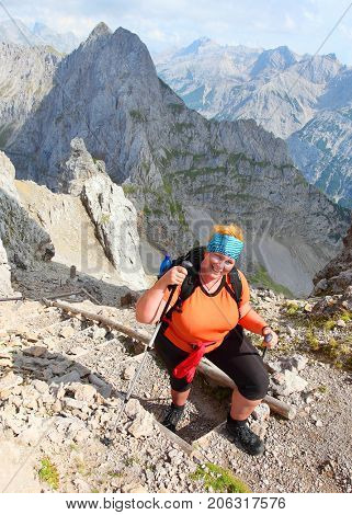 Overweight woman nordic walking. Successful slimming  in alpine landscape. Healthy lifestyle and weight loss concept. Karwendel Alps, Bavaria, Germany.