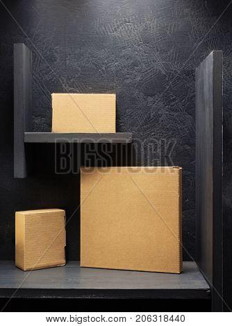 cardboard box on wooden shelf black background surface