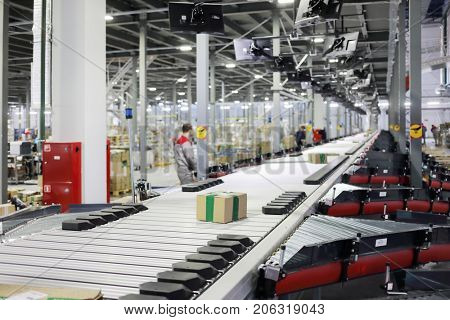 Workers in modern workshop with conveyor, many displays in warehouse