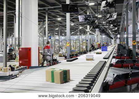 People work in modern workshop with conveyor, many displays in warehouse