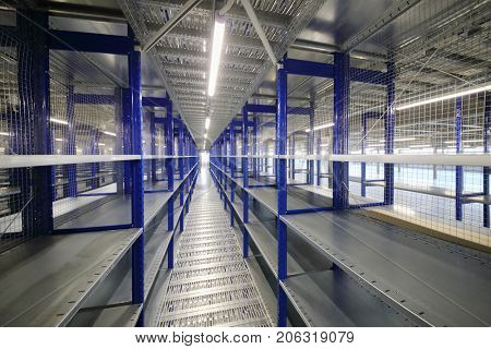 Big empty warehouse with many shelves - long hallway in sorting center