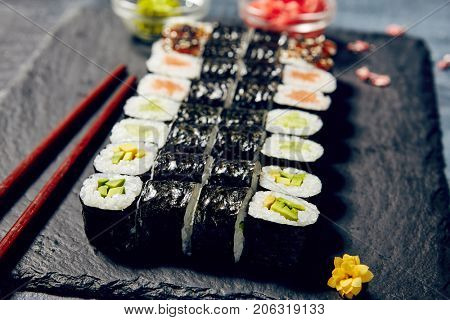 Beautifully served sets of sushi rolls with fish, rice and vegetables next tо wasabi and ginger with chopsticks, greens and flowers on dark copyspace background