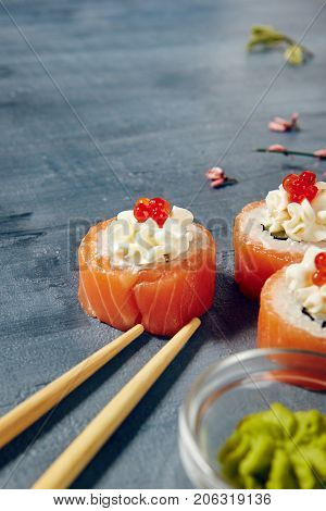 Beautifully served sets of philadelphia sushi roll with fish, rice,cream cheese next tо wasabi with chopsticks, greens and flowers on dark copyspace background
