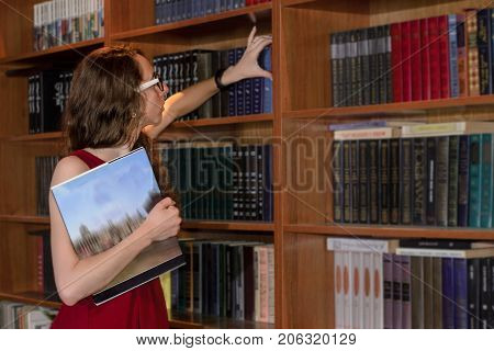 Young woman reaching for a book from a tall wall mounted book case. Girl with a book in her hand