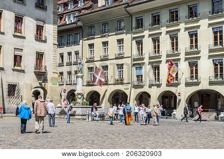 Bern Switzerland - May 26 2016: People on Munsterplatz square in the old city center of Bern Switzerland. Decorative Moses Fountain can be seen on the Munsterplatz.