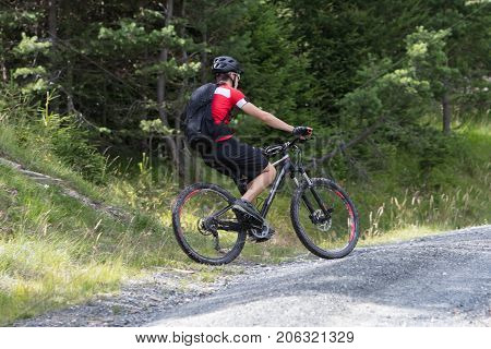 Urecognisable Mountainbiker On A Gravel Road