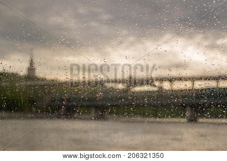 A view from the ship to the river landscape and the bridge through the Wet, wet cabin glass.