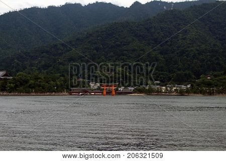 Gate Temple By The Beach. Far-away Look Of Itsukushima Shrine In Miyajima Island, Japan. The Gate Is