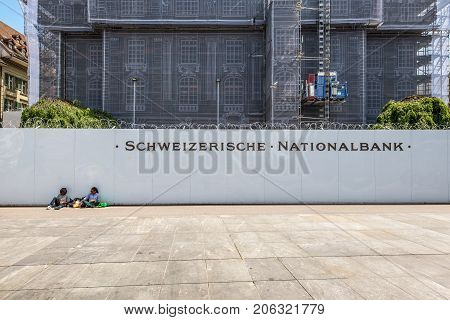 Bern Switzerland - May 26 2016: People are resting near National Bank of Switzerland in Bern Switzerland. Building facade covered for restoration work.